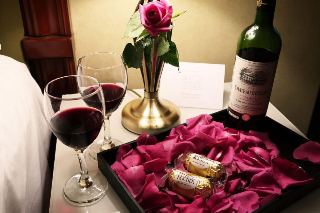 Romantisches Arrangement aus Wein, Pralinen und Rosen